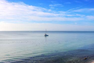 Ruhiger Strandtag mit Segelboot